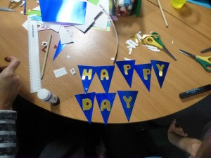 A picture of some blue and gold bunting that says happy day