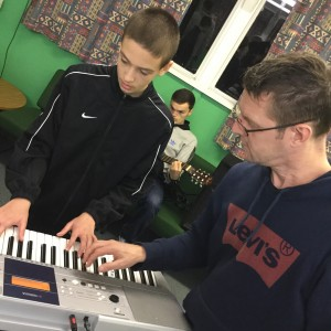 young person being shown how to play keyboards