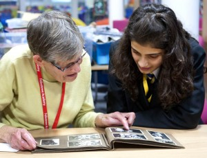 Adult talking about a black and white photograph to a pupil