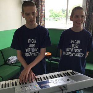The twins standing at a keyboard