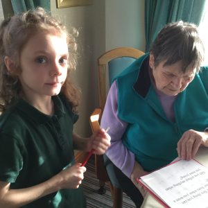 The picture shows a primary school Year 3 pupil together with a resident from Broadlands Care Home