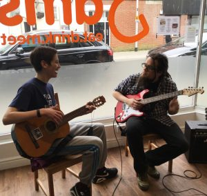 Dan Ball and participant playing guitar