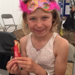 A young girl proudly showing off the peg doll she made at the Lowestoft Folk craft activity.