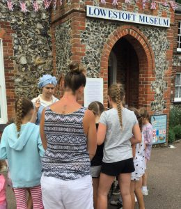 Five young children and an adult watch intently as a woman dressed in a Victorian bathing costume tells them a story about Lowestoft Museum.