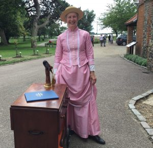 A woman, dressed in a Victorian outfit of long, gathered skirt and long sleeved jacket with tiny pink buttons, standing outside Lowestoft Museum with a museum exhibit