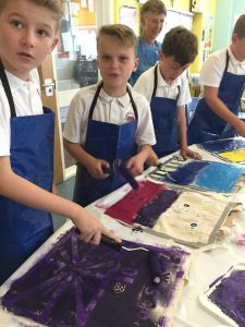 A row of four young boys in blue aprons, applying paint to canvas bags