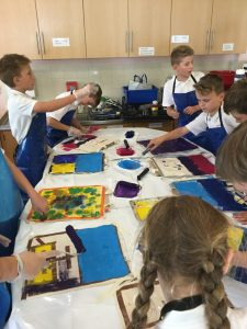 A group of school children gathered round a table, using rollers to apply bright acrylic paint to their canvas tote bags