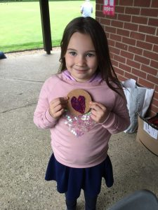 A young girl holding a small round mat on which she has created a heart-shaped pattern in tap work using small pins and silk threads