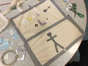 A plain cotton tote bag has been decorated with taped letters and a figure, ready to be painted