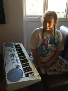 A young girl with long braids sits at a keyboard, sunlight from the window illuminating one side of her face