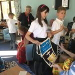 Children showing their decorated story bags to the residents