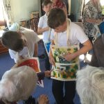 A student showing his story bag to a resident