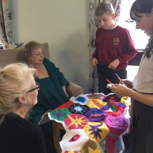 A group of residents and students discussing a brightly coloured felt quilt
