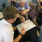 A young participant showing a resident a drawing