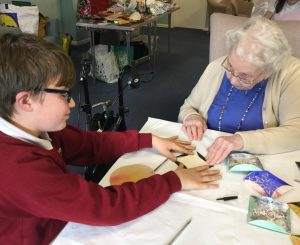 An elderly resident working with a school child, as they make paper quilt pieces together