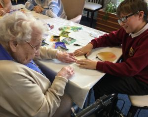 A school pupil and resident working in pairs to create artwork