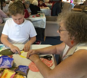 A child and adult making paper quilt pieces and in the background, tables full of other participants, working together