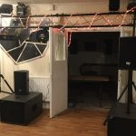 An open door is flanked by two large speakers with a gantry overhead decorated with strings of party lights