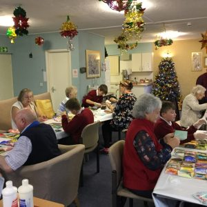 Adults and children working together, pasting paper patchwork quilts. The room is decorated for Christmas and in the background a Christmas tree is covered with baubles and lights