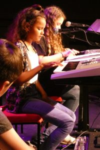 Two girls playing keyboards