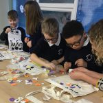 Four school children choosing sticky letters to stick on their story bags