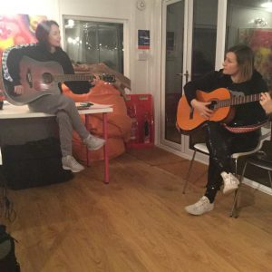 A young woman sits on a table, holding a guitar whilst the music tutor shows her a guitar chord.