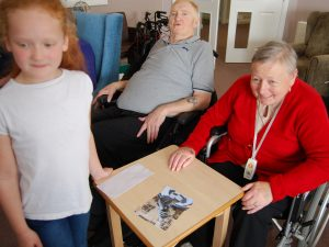 Two Britten Court residents together with a pupil with a homemade jigsaw puzzle on the table in front of them.