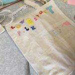 A blank canvas tote bag has been decorated with stick on letters spelling Lowestoft Folk and strips of masking tape, read for the bag to be painted, after which the tape and letters will be peeled off, to reveal the patterns underneath.