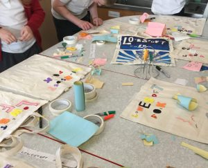 A table is strewn with rolls of masking tape, coloured pens and bits of sticky back plastic. There are scissors and scraps of paper and at least two children sticking tape down onto canvas tote bags.