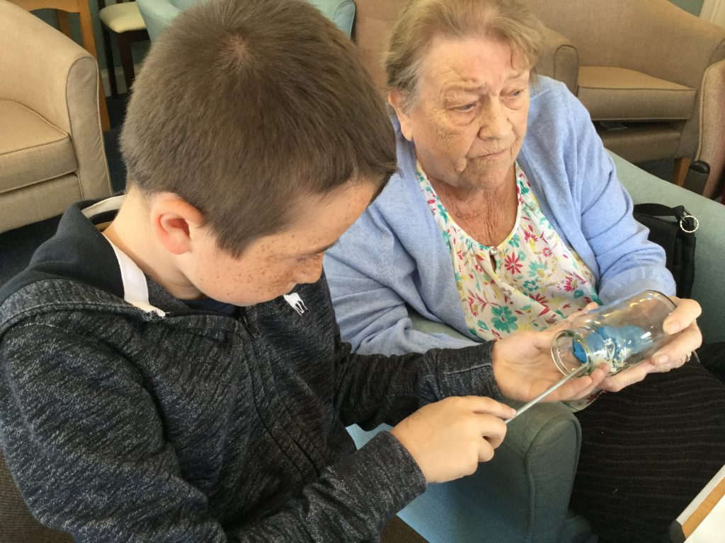 A young boy is using a long metal tent peg to push plasticine into a glass bottle that is held by one of the residents