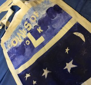 A close up of a painted canvas tote bag. The top half is painted shades of light and medium blue, resembling the sea with the sky above and has the words Lowestoft Folk across it. The bottom half of the bag is a much darker blue and has stars and the moon on it.