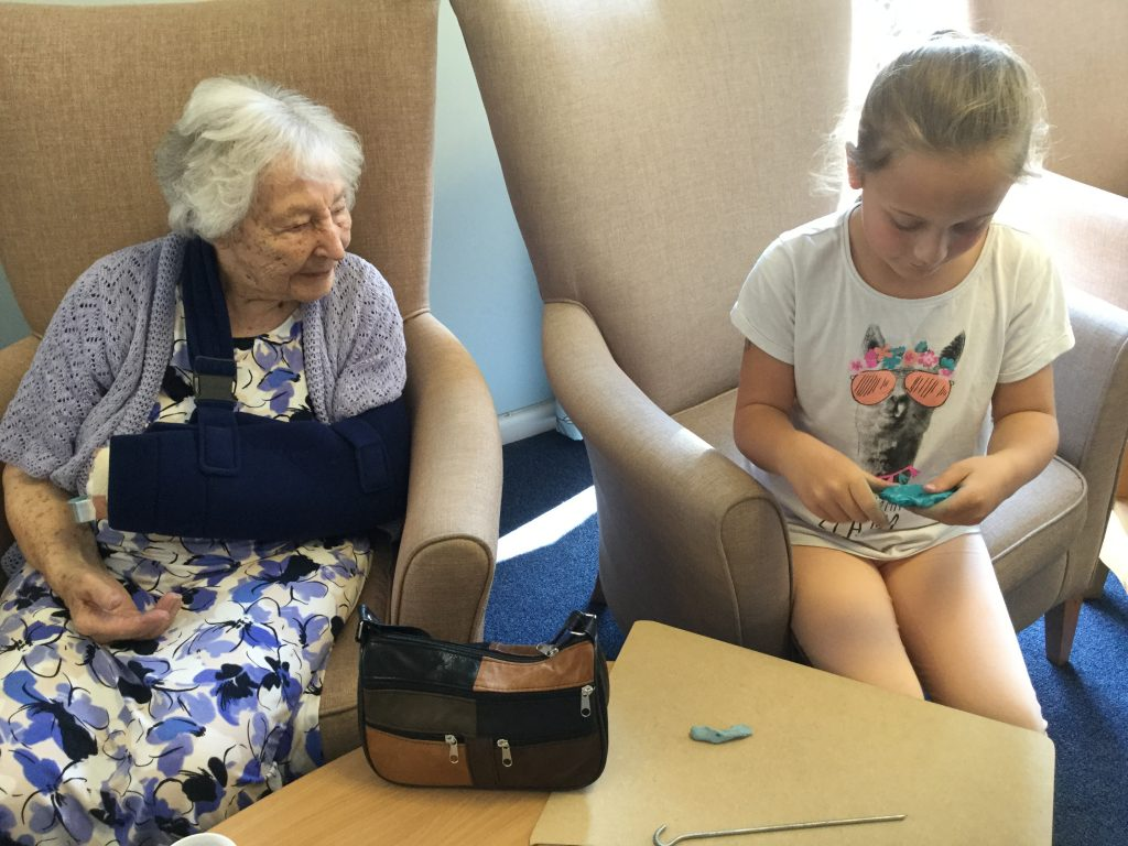 A young girl is sitting next to one of the residents, who looks on as the young girl works a piece of turquoise plasticine in her hands