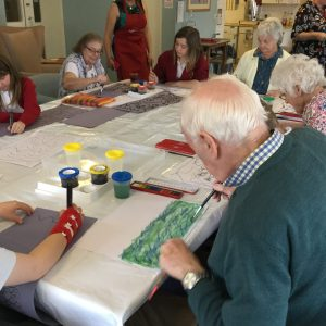 Adults and children seated round a table. Some are using black felt tip pens, others are using printing ink and watercolour, to create patterns and images inspired by the music being played.