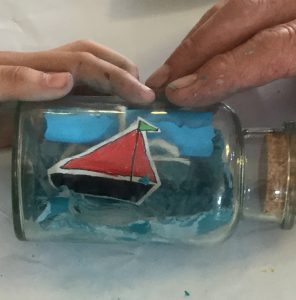A boat in a bottle on top of which are two hands, one of a child and the other an adult's, with flakes of plasticine on them