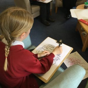A young pupil, mark making in response to the music being played.