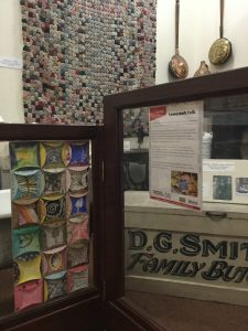 An image of the Domestic Objects collection at Lowestoft Museum. On the wall there are two copper warming pans and also a large hand stitched quilt made out of Suffolk Puffs, a particular form of quilting in which circles of fabric are stitched and then gathered up into small, puffy pouches and then sewn together to make the large quilt. In the foreground there is a card and paper version of the quilt, in which circles of card have been printed and decorated and then glued together to form a larger piece of art.