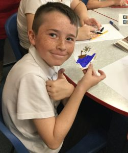 A school pupil gives a thumbs up whilst showing the scallop shell he has decorated