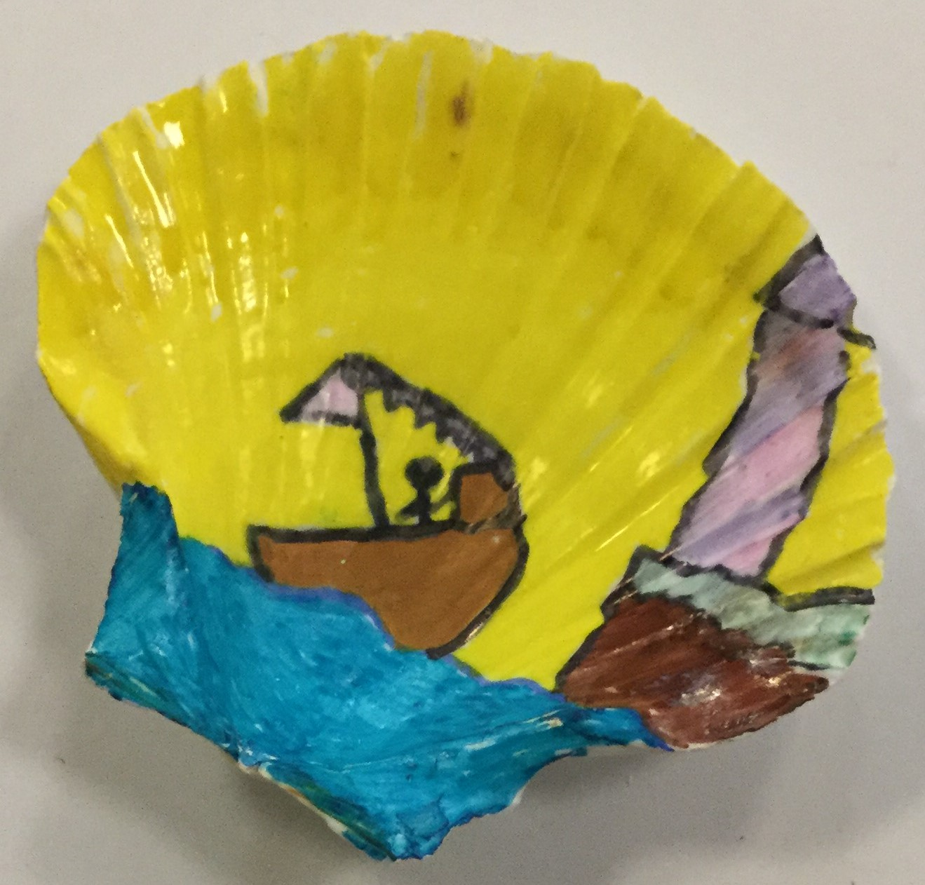 The inside of the scallop shell has been decorated with a brilliant yellow sky and turquoise sea. A boat, complete with pink sail and small figure is entering the harbour mouth, with a lighthouse perched on the wall to the right