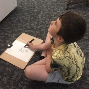 The image shows a young boy staring intently at an object that is out of view whilst drawing it in black ink on a piece of paper in front of him.