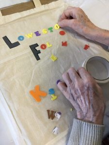 The image shows a pair of hands, obviously of an elderly person, delicately placing a sticky-backed letter on to a bag as she spells out the word Lowestoft