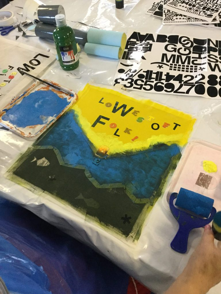 A decorated canvas bag, the top half bright yellow with the words Lowestoft Folk clearly visible and the bottom half a deep blue descending into black at the bottom of the picture. Around the bag there are sheets of sticky-backed letters, rollers and a bottle of green acrylic paint