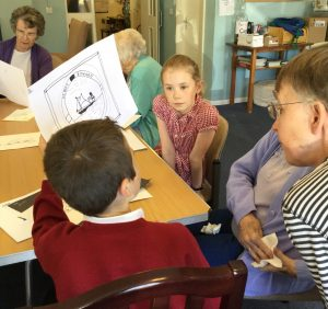 A young boy is showing his drawing of a boat inside a round frame, as another child and adults look on