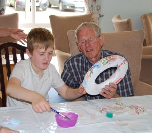 A young boy dipping a brush in a pot of glue whilst the man beside him is holding a polystyrene ring onto which they are pasting pieces of decorated paper