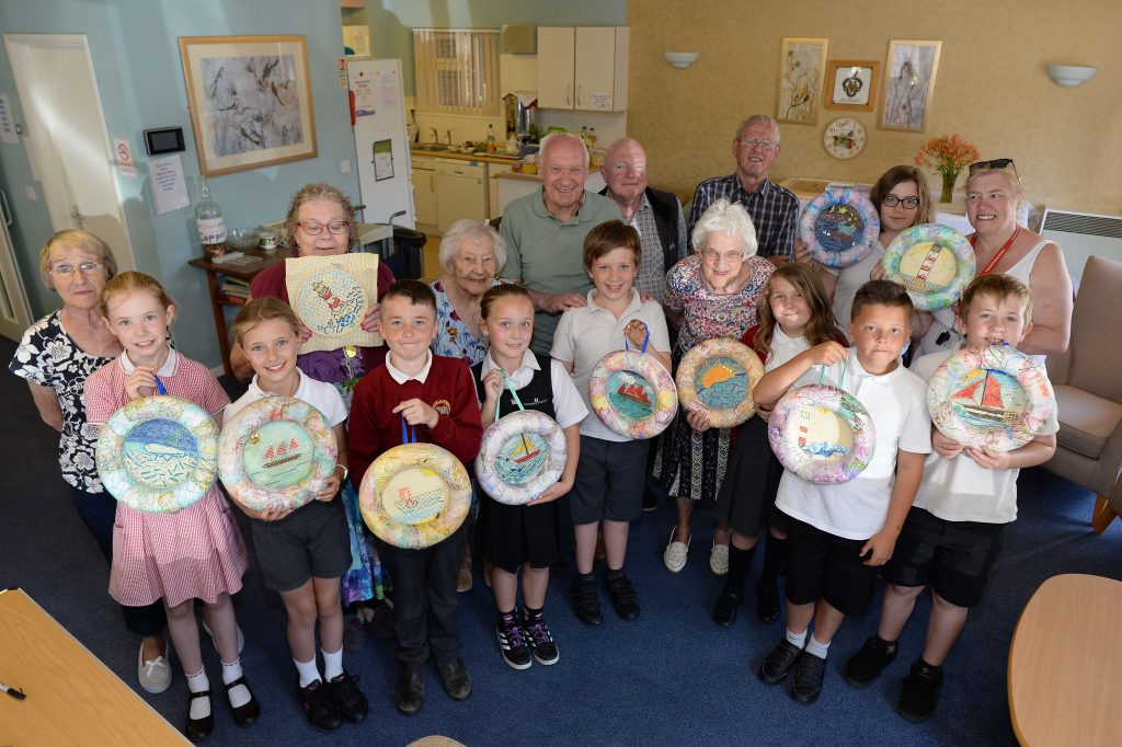 The Lowestoft Folk participants holding the embroidered pictures they made together