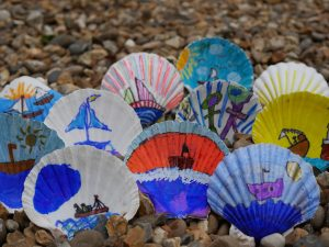 A collection of scallop shells that are decorated with brightly coloured pictures of ships