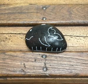 A whale, painted onto a beach pebble