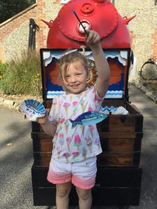 A young girl stands in front of the Sea Chest holding up a scallop shell she has decorated along with the fish she made