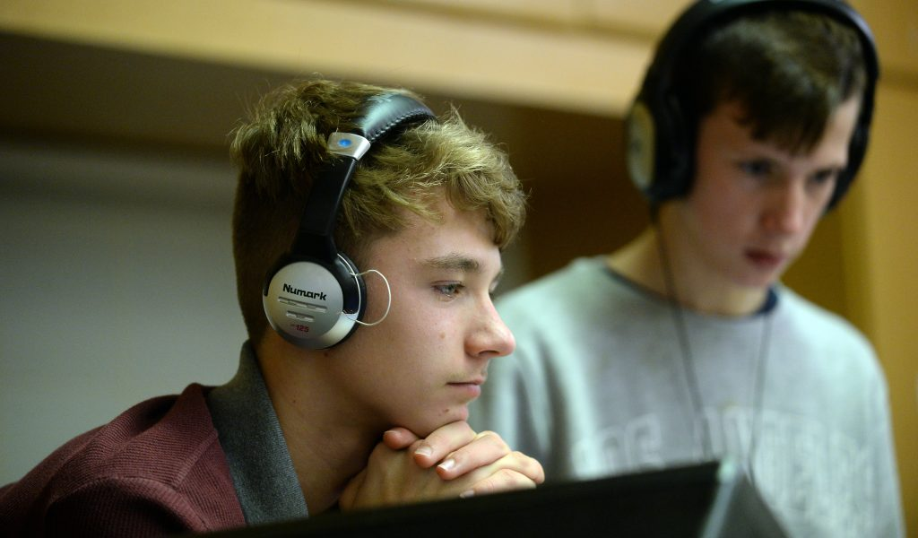 In the foreground, a young man with headphones stares intently at the DJ screen, whilst his partner stands behind, also watching the DJ decks
