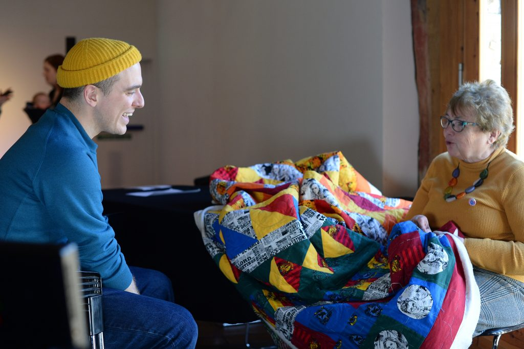 Dancer Tim Casson chatting to a woman as she works away at a large quilt