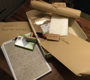 A collection of brown envelopes, pens and paper, plus a copy of a hand-written letter